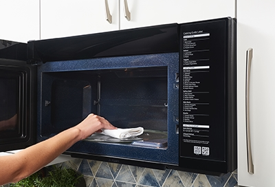 Person cleaning the inside of their microwave