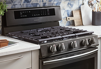 A Samsung slide in gas range in front of a blue triangle-tiled backsplash