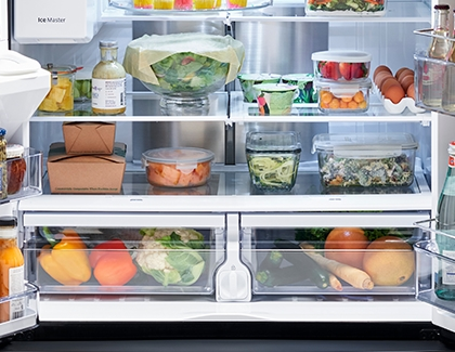 Lower shelves of a Samsung Fridge with eggs, salad, vegetables, and containers of leftovers