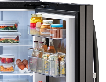Right side door of a Samsung fridge filled with condiments, juice, and soda