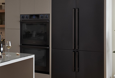 Samsung Four Door Flex refrigerator next to a duo wall oven