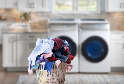 Laundry basket with a stack of clothes with washer in the background