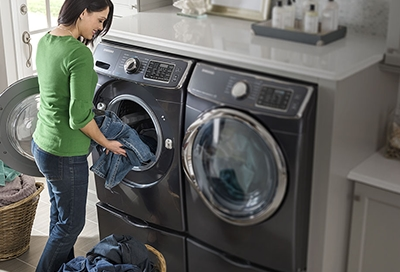 Woman in green shirt pulling jeans out of the washer