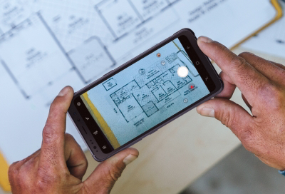 Person taking photo of a blueprint with Samsung phone