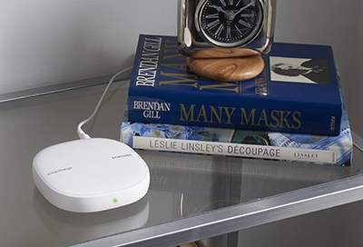 SmartThings Wifi Hub on a table with books