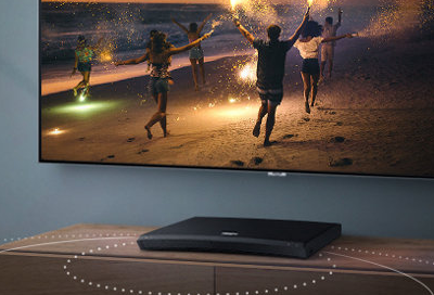 Samsung Blu-ray player below a TV mounted on the wall