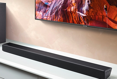 Soundbar sitting on a table in front of a mounted Samsung TV
