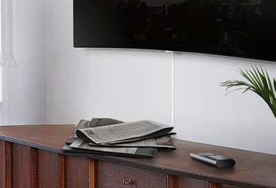 TV with a One Connect cable running down and behind a cabinet, where no one can see it