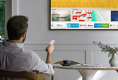 Man with samsung remote connected to the Smart TV