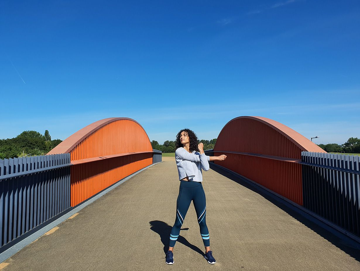 Photo captured by the Wide-angle Camera of a woman stretching on a bridge with grey gating and orange accents against a bright blue sky