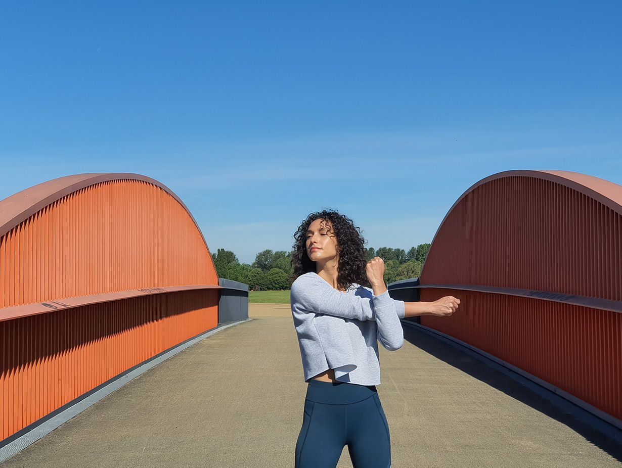 Photo captured by the Telephoto Camera of a woman stretching on a bridge with grey gating and orange accents against a bright blue sky