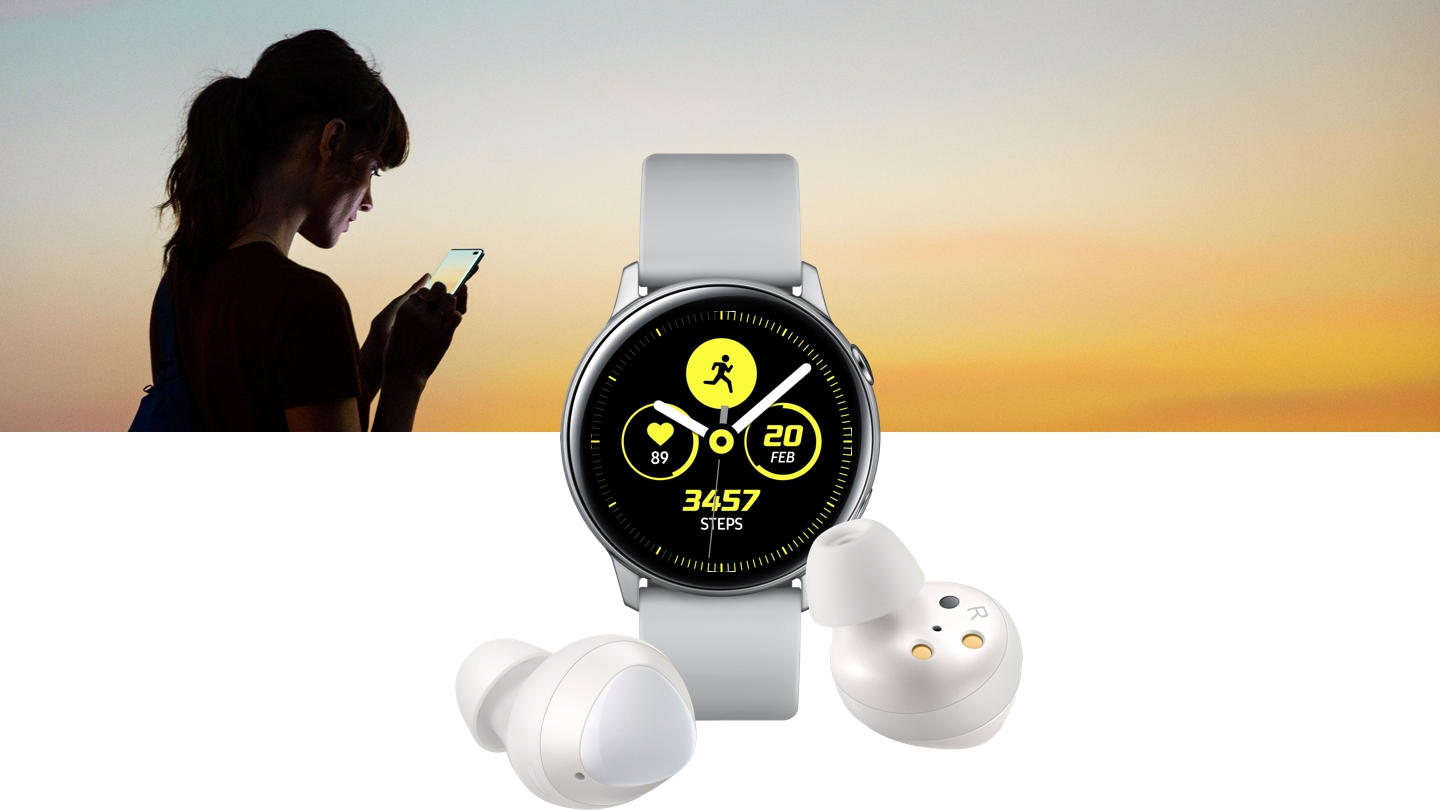 The silver Galaxy Watch Active upright with an exercise screen on its face, and two white Galaxy Buds in front in different positions. Behind the products is a woman looking at her phone set against a sunrise gradient.