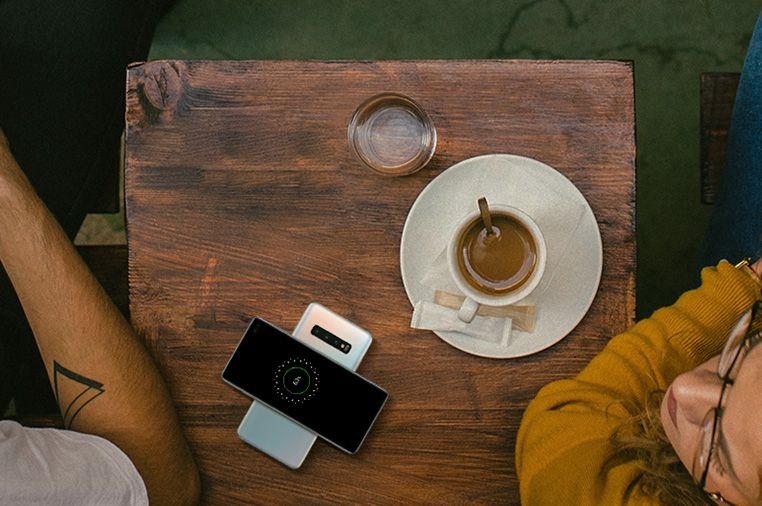 Samsung Galaxy S10 Featuring Wireless PowerShare - Table in Coffee Shop with Man and Woman Charging S10 using Another S10
