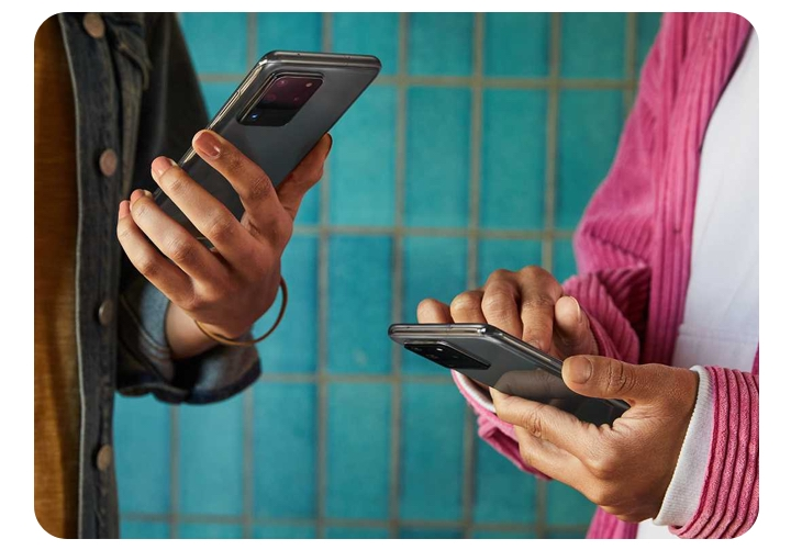 Close up shot of two people holding phones. The hand on the left is tiling the phone upward slightly while the other person is holding the phone and tapping it with the other hand.