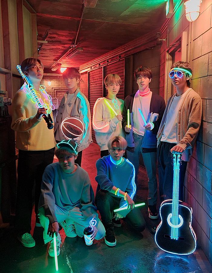 Фотографии, сделанные в ночном режиме на Galaxy S20 plus.  BTS стоит в слабо освещенном коридоре, держа предметы, освещенные светящимися палочками и неоновым освещением, такие как гитара, кларнет, баскетбол, солнцезащитные очки и многое другое.  В режиме «Ночь» на фотографии вы можете видеть очертания участников группы, но в основном это светящиеся палочки и неоновые объекты.  В ночном режиме на фотографиях лица и наряды группы выглядят намного четче и красочнее