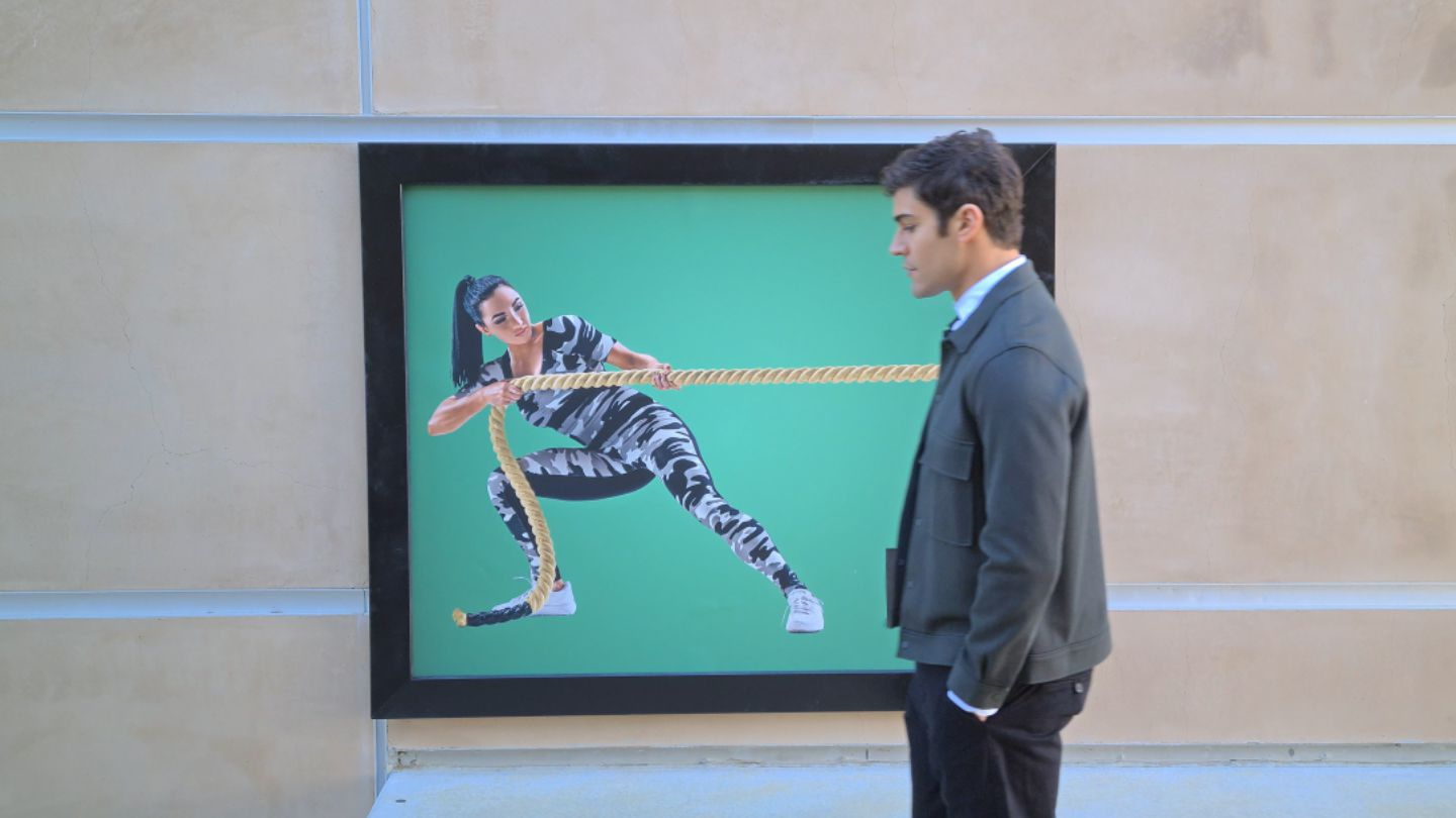 People walking on the street in front of an ad for a fitness center, with a woman pulling on a big rope. The video timeline reverses until we see a man walking in front of the fitness center ad, appearing to be pulled by the rope. The 8K video snap icon appears and is tapped, capturing a still of that moment