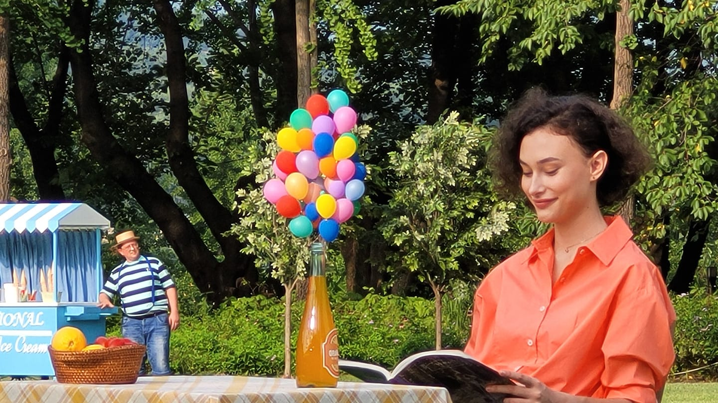 10x zoomed in photo, getting even closer to the woman sitting alone at a table. More details become clear, like that she's reading a magazine and on top of the table is a bunch of many mini balloons and an orange bottle.